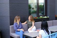 Jeunes amis féminins parlant au café et s'asseyant sur le sofa Photos stock