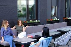 Jeunes amis féminins parlant au café et s'asseyant sur le sofa Photographie stock