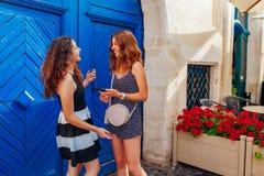 Jeunes amis féminins parlant tout en à l'aide du smartphone par le café Belles femmes heureuses riant et ayant l'amusement Photos stock