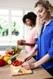 Jeunes amis féminins préparant la nourriture Images stock
