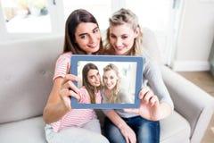 Jeunes amis féminins prenant le selfei à la maison Images stock