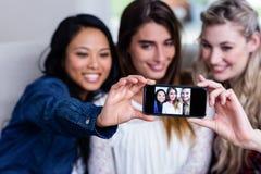 Jeunes amis féminins prenant le selfie avec le téléphone portable Images libres de droits