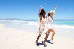 Jeunes amis féminins riant et jouant sur la plage Photos stock