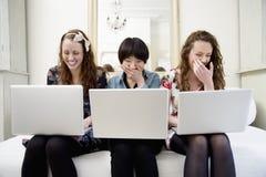 Jeunes amis féminins riants s'asseyant sur le sofa Photographie stock libre de droits