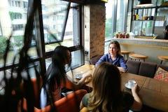 Jeunes amis féminins s'asseyant au café de restaurant, de parler et de boissons Image stock