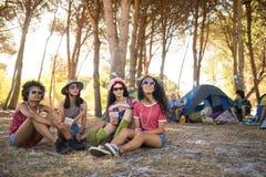 Jeunes amis féminins s'asseyant au terrain de camping Photo stock