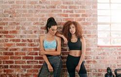 Jeunes amis féminins se tenant contre le mur dans le gymnase Photo libre de droits