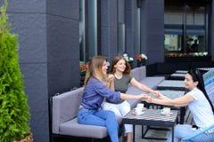 Jeunes amis féminins tenant des mains au café et buvant du café Photo stock
