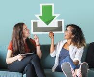 Jeunes amis féminins tenant une icône de téléchargement images libres de droits