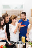 Jeunes amis faisant cuire le dîner ensemble Photo libre de droits