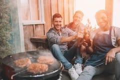 Jeunes amis faisant le barbecue et buvant de la bière sur le porche avec la lumière arrière Photo libre de droits