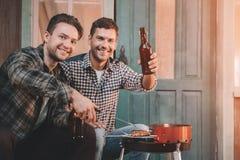 Jeunes amis faisant le barbecue et buvant de la bière sur le porche avec la lumière arrière Photos libres de droits