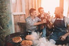 Jeunes amis faisant le barbecue et buvant de la bière sur le porche avec la lumière arrière Photographie stock