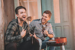 Jeunes amis faisant le barbecue et buvant de la bière sur le porche avec la lumière arrière Image libre de droits