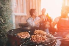 Jeunes amis faisant le barbecue sur le porche avec la lumière arrière Photographie stock