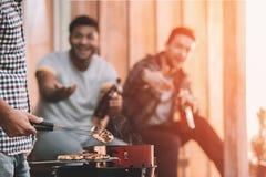 Jeunes amis faisant le barbecue sur le porche avec la lumière arrière Photo stock