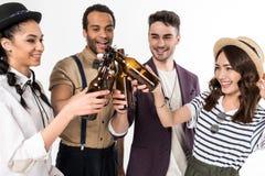 Jeunes amis faisant tinter des bouteilles à bière d'isolement sur le blanc Image libre de droits