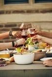 Jeunes amis faisant tinter des verres à vin dans un pain grillé Photo libre de droits