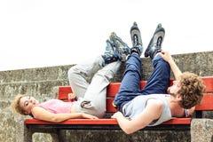 Jeunes amis fatigués de personnes détendant sur le banc Photos stock