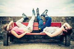 Jeunes amis fatigués de personnes détendant sur le banc Photos libres de droits