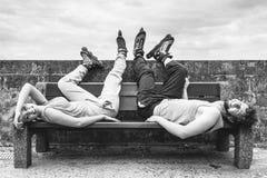 Jeunes amis fatigués de personnes détendant sur le banc Image stock