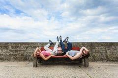 Jeunes amis fatigués de personnes détendant sur le banc Photographie stock