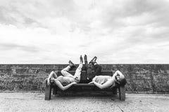 Jeunes amis fatigués de personnes détendant sur le banc Photographie stock libre de droits
