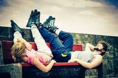 Jeunes amis fatigués de personnes détendant sur le banc Photo libre de droits