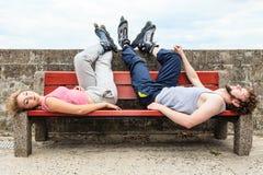 Jeunes amis fatigués de personnes détendant sur le banc Images libres de droits