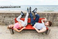Jeunes amis fatigués de personnes détendant sur le banc Photo stock