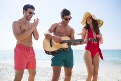 Jeunes amis gais appréciant à la plage Images stock