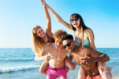 Jeunes amis gais appréciant l'été sur la plage Images libres de droits