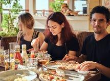 Jeunes amis gais appréciant la nourriture et ayant l'amusement ensemble dans le restaurant ou le café extérieur photo libre de droits