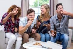 Jeunes amis gais appréciant la pizza Photographie stock