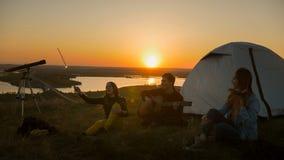 Jeunes amis gais ayant l'amusement ensemble et jouant la guitare au coucher du soleil sur la colline Photographie stock libre de droits
