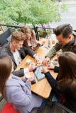 Jeunes amis gais causant au café sur le fond d'extérieur Concept d'amitié Images stock