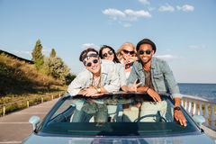 Jeunes amis gais conduisant la voiture en été Images stock