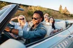 Jeunes amis gais conduisant la voiture et souriant en été Image stock