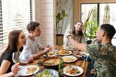 Jeunes amis gais mangeant et ayant l'amusement à la table Photos libres de droits