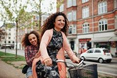 Jeunes amis gais montant une bicyclette dans la ville Image libre de droits