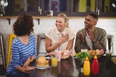 Jeunes amis gais parlant tout en se reposant avec la nourriture et la boisson au café Images stock