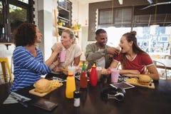 Jeunes amis gais partageant la nourriture au café Photos stock