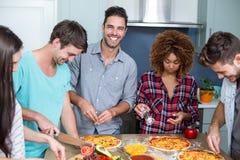 Jeunes amis gais préparant la pizza à la maison Images stock