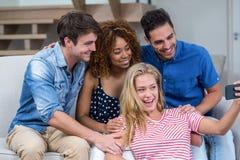Jeunes amis gais prenant le selfie à la maison Photographie stock