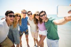 Jeunes amis gais prenant le selfie à la plage Photo stock