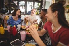 Jeunes amis gais s'asseyant avec la nourriture et la boisson à la table Photos stock