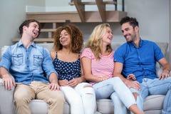 Jeunes amis gais s'asseyant sur le sofa Photographie stock libre de droits