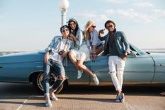 Jeunes amis gais se tenant près de la voiture Photo stock
