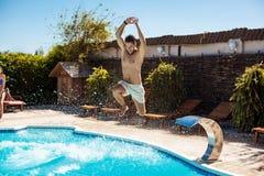 Jeunes amis gais souriant, détente, sautant dans la piscine Image stock
