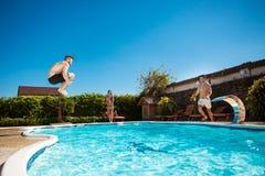 Jeunes amis gais souriant, détente, sautant dans la piscine Photo stock